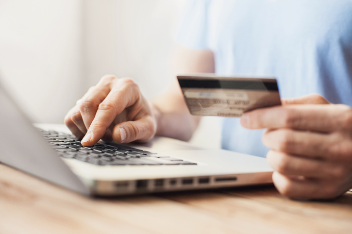 Person using credit card to buy something on laptop.