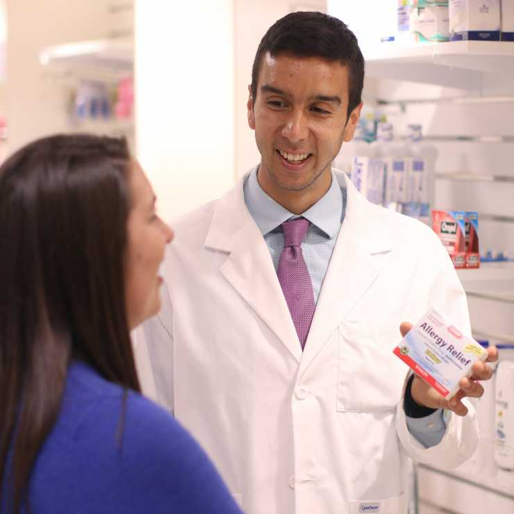 Pharmacist showing patient medicine